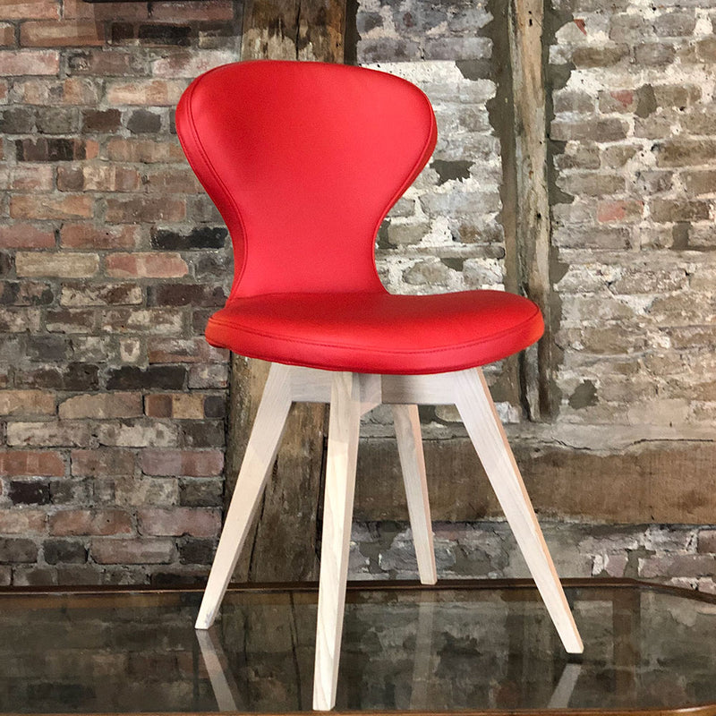 R1 leather dining chair with oak legs, shown in red