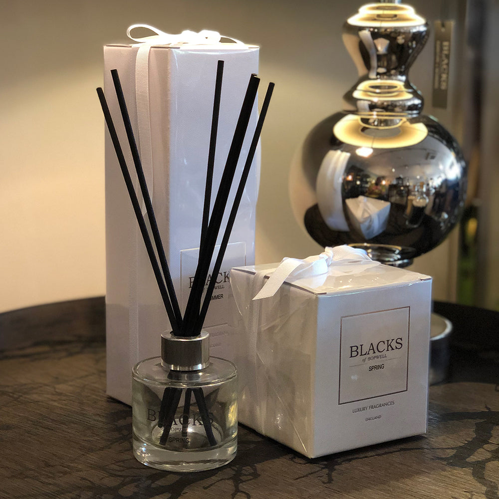 clear glass diffuser, clear label black writing.black reed, shown with white box packaging and white boxed candle.