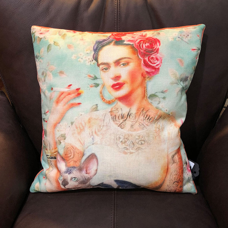 cushion front shows frida kahlo smoking a cigarette, body covered with tattoos, sphynx cat on her lap.