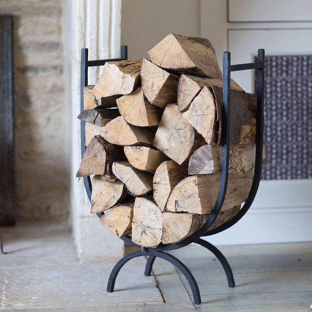 black wrought iron U shaped log stack shown with logs