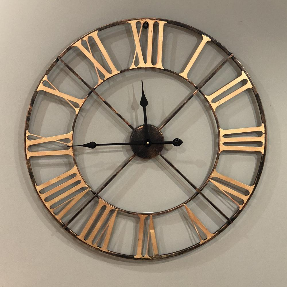 large skeleton clock with brass colour roman numerals against grey wall