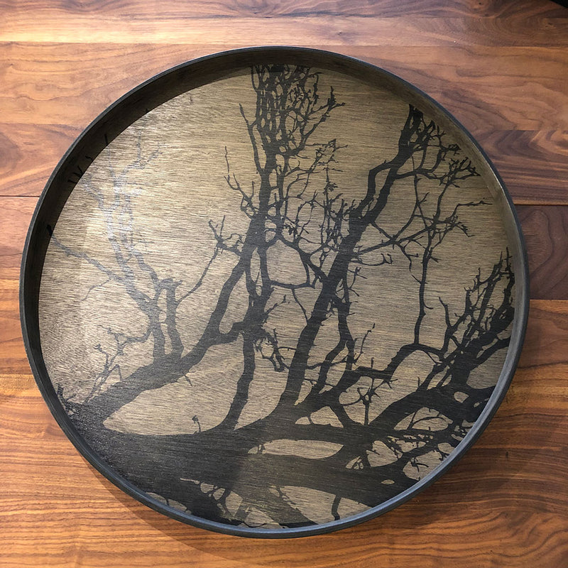 Large round black tray with silhouette of a black tree and branches