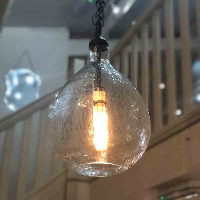 glass shade industrial pendant light, showing vintage style bulb. dark metal chain and fitting.