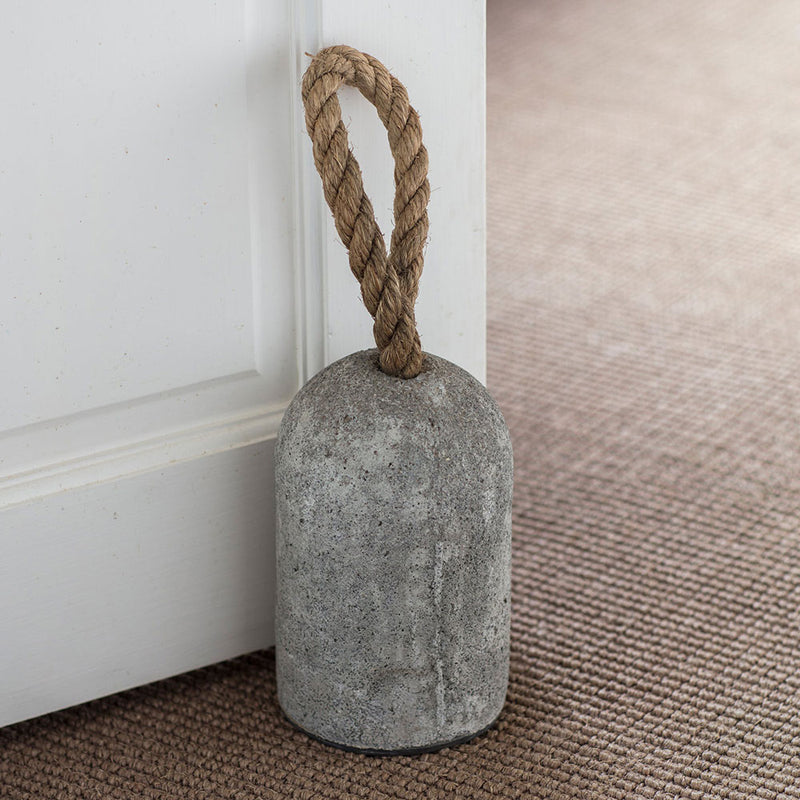 grey cement doorstop, bullet shaped, with a jute rope handle