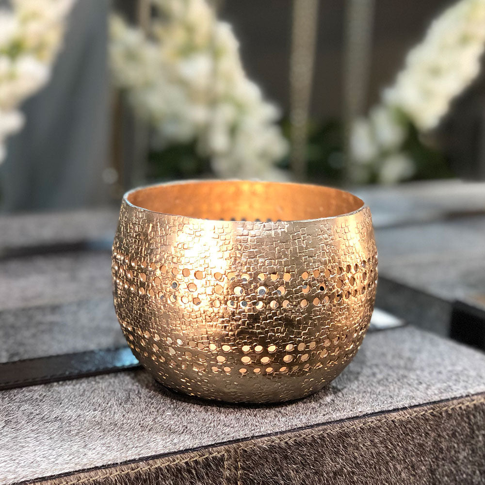 round bowl shaped votive holder with a golden finish. cut away holes for the light to show through.