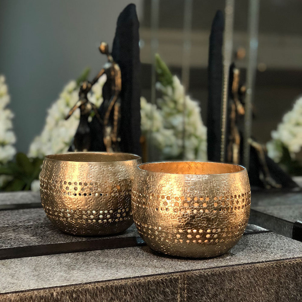 pair of golden votive holders shown on a tabletop.