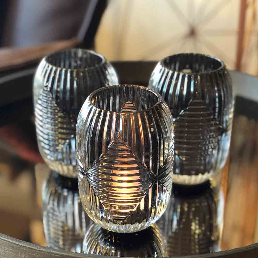 glass candleholder with etched diamond shaped ribbed in the glass. tealight lit inside.