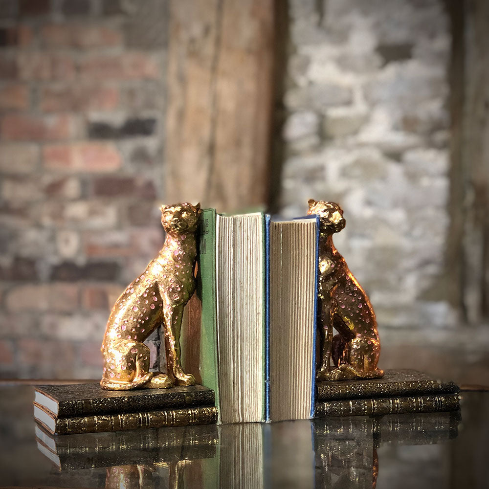 gold cheetah book ends, each animal supporting the books.