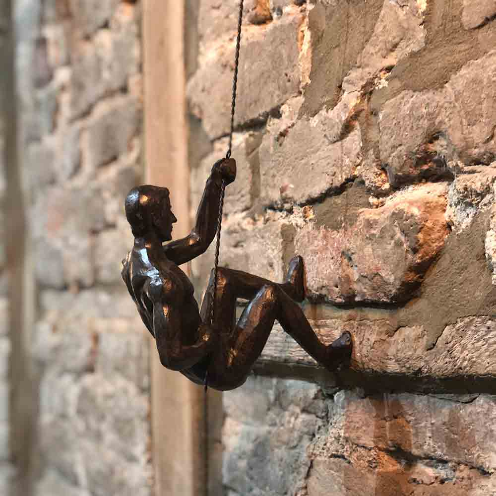 bronze colour climbing nude figure, pulling up a rope.