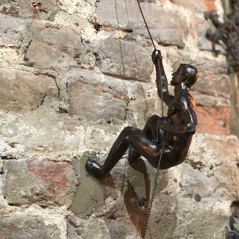 bronze climber on wire, hanging from the brick wall