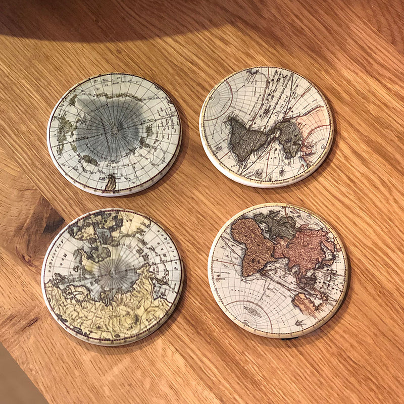 set of four globe coasters on coffee table. vintage map design