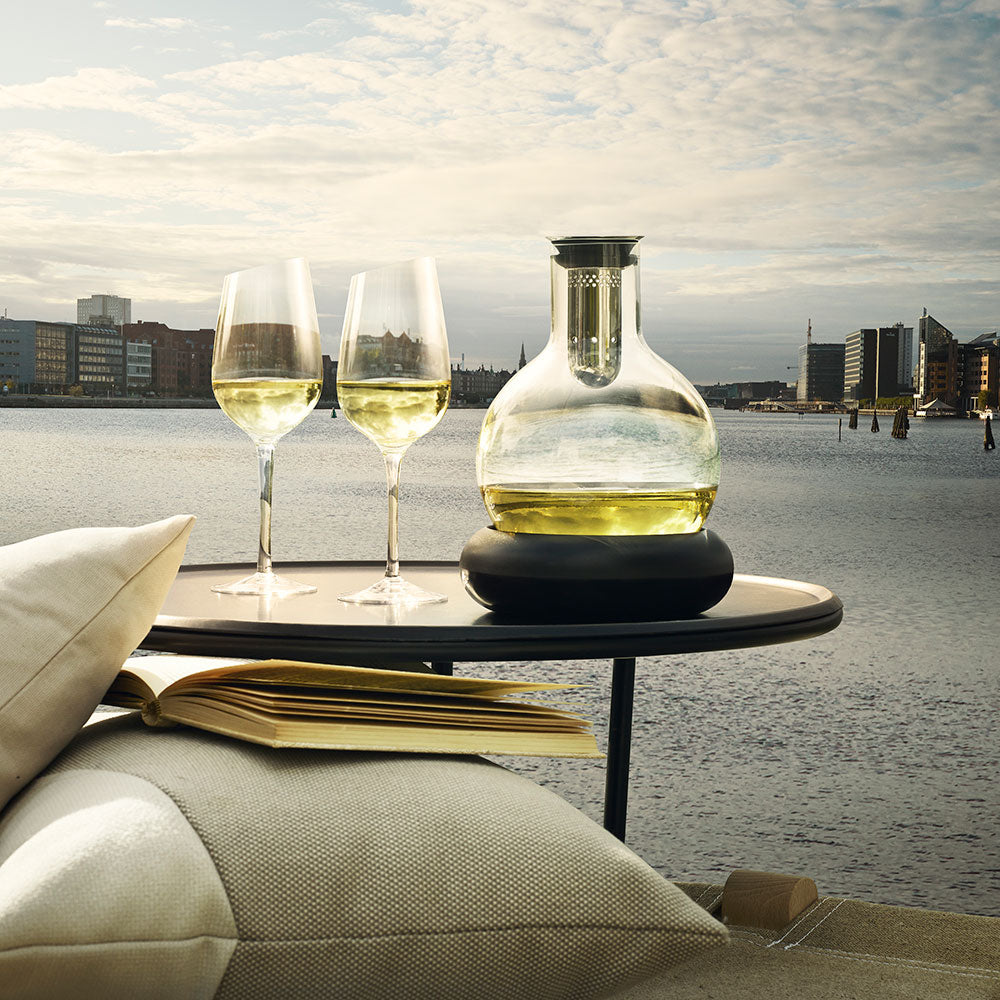 Cool decanter shown with white wine in an alfresco setting