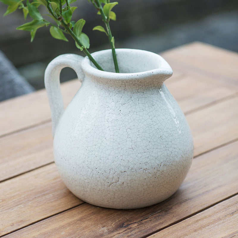 white glazed jug for floral arrangements, shown with stems of foliage. crackle finish glaze.