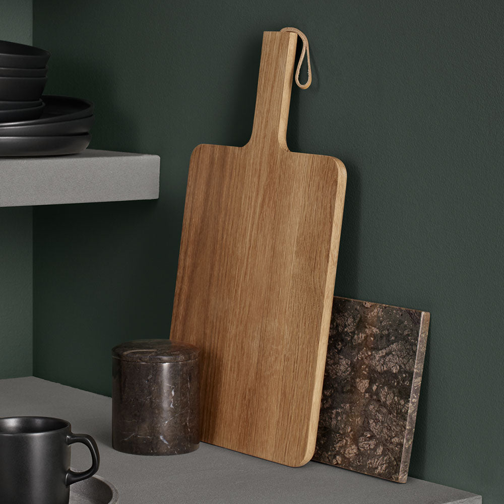oak chopping board shown leaning upright against the wall of a kitchen counter
