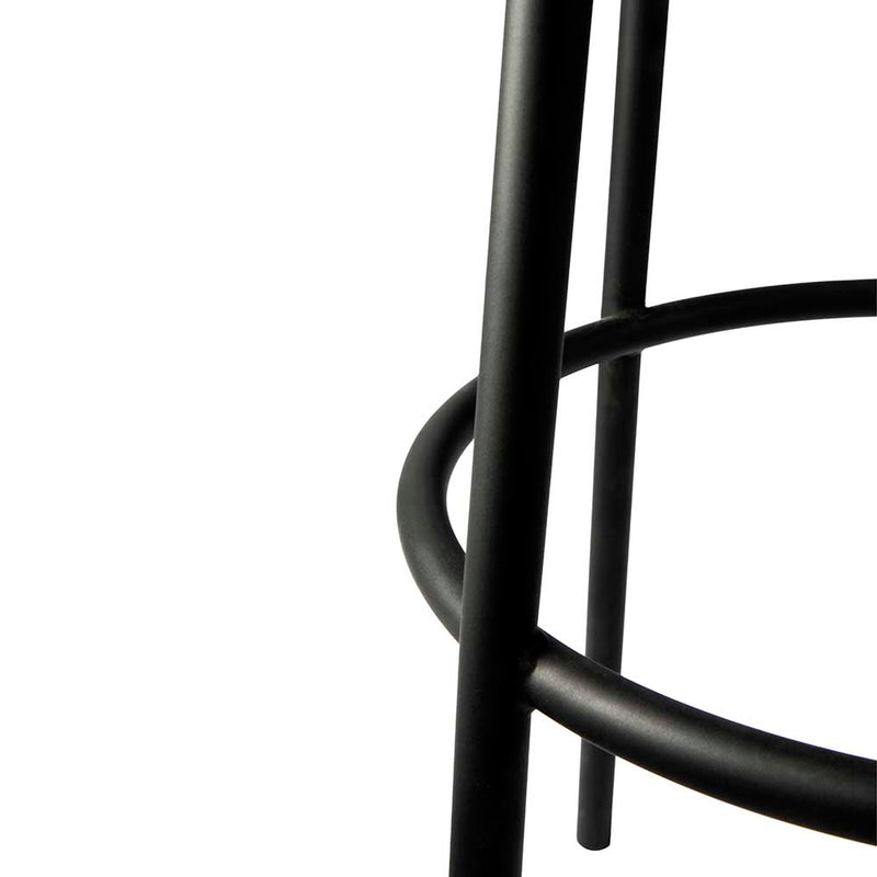 detail of black rounded metal leg frame and foot rest.