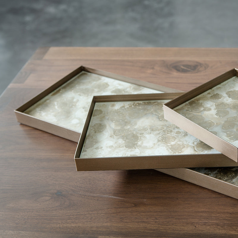organic collection of trays, stacked showing sides of the metal edging.