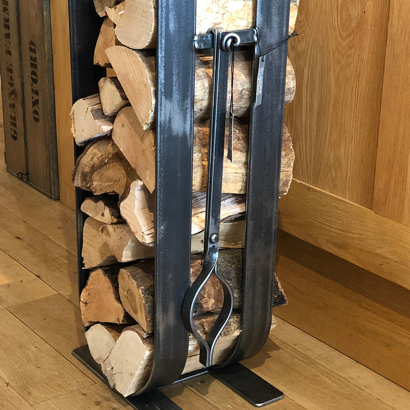 Fire tongs shown hanging on a log holder.