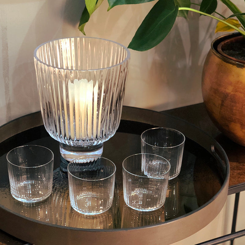 pleated glass hurricane shown on sideboard with ribbed glass tumblers