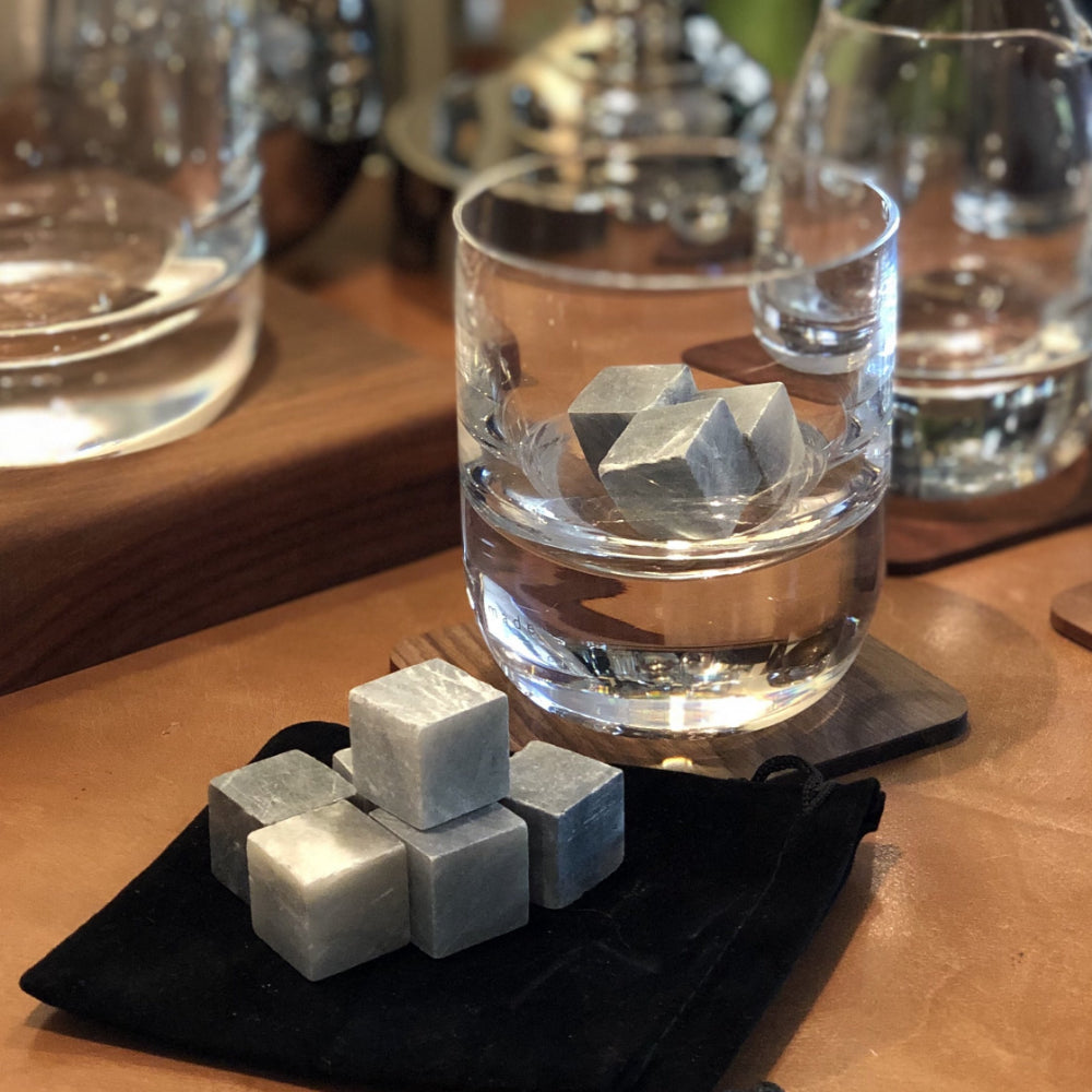drinks stones, shown in a whisky glass, they are grey mineral cubes.