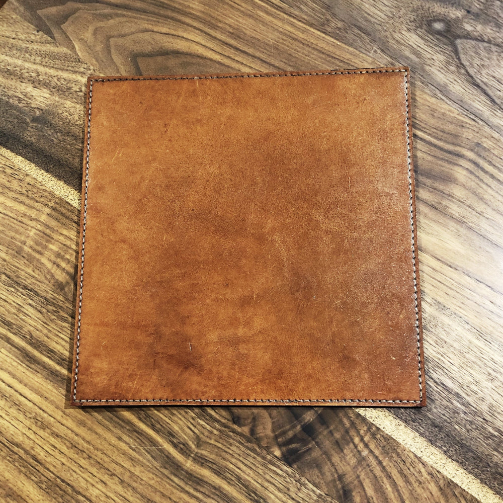 brown leather mouse mat, stitching around edges,