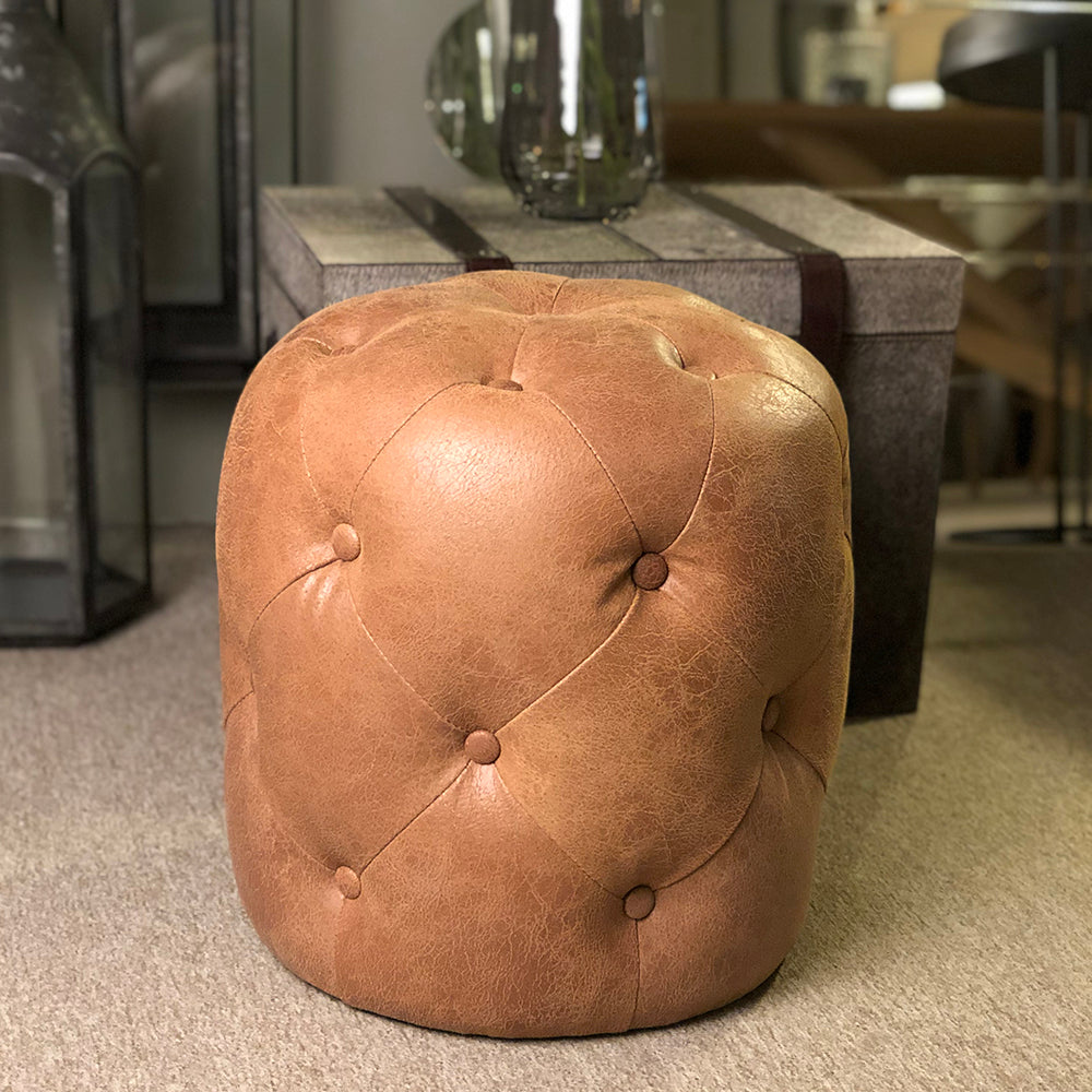 Tan leather stool, brown distressed leather with buttoning detail.