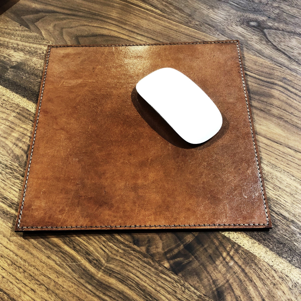brown leather mouse mat shown with mouse.