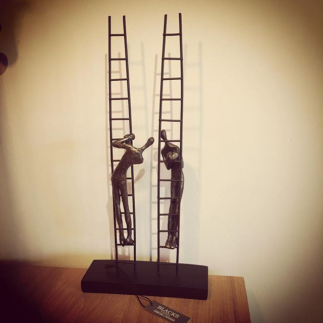 sculpture of two upright ladders each with climbers facing