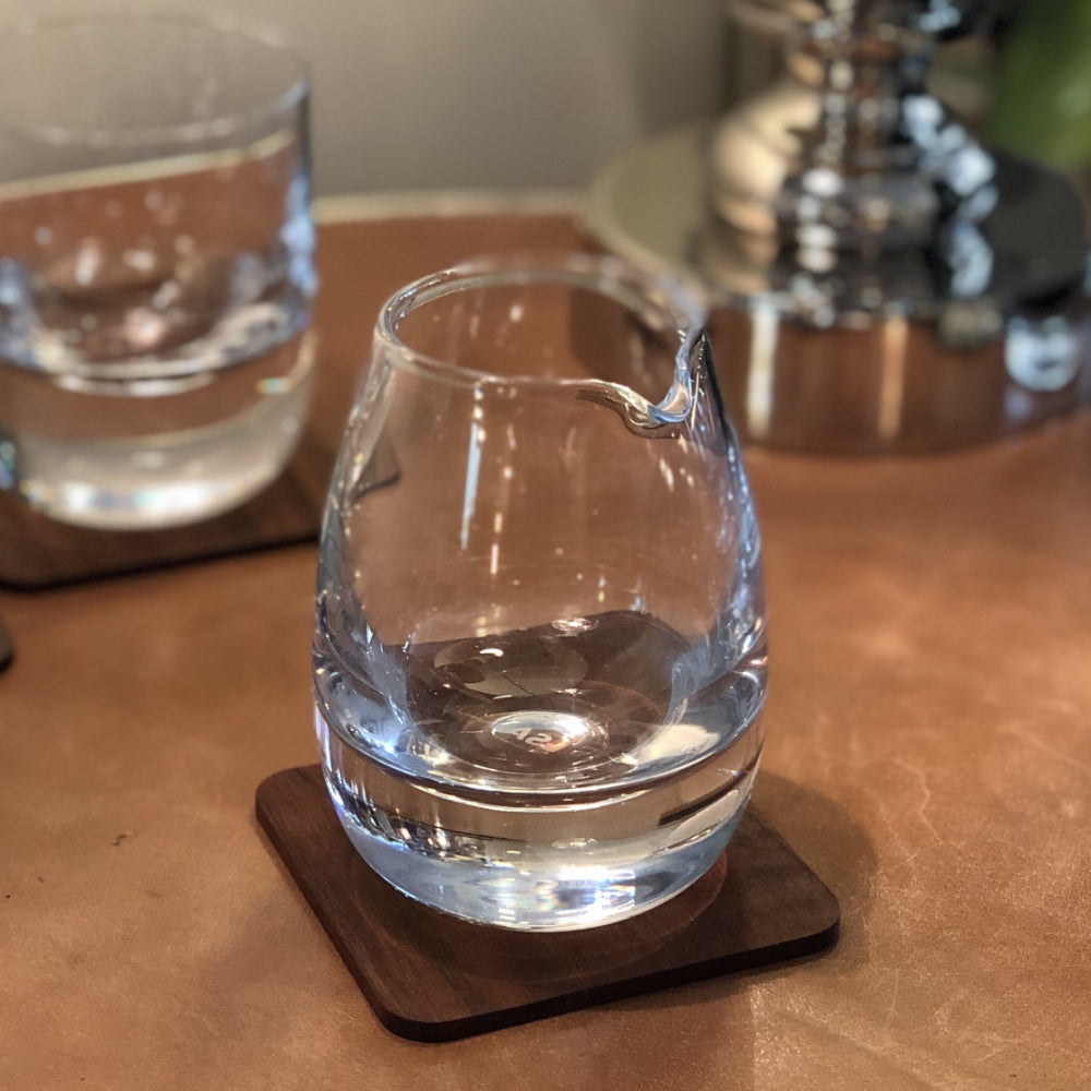 glass whiskey water jug on walnut coaster