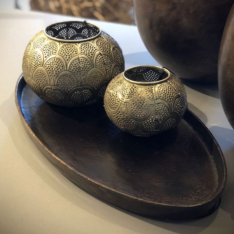 large and small votives shown from side on a tabletop, ball shaped with open filigree work metal.