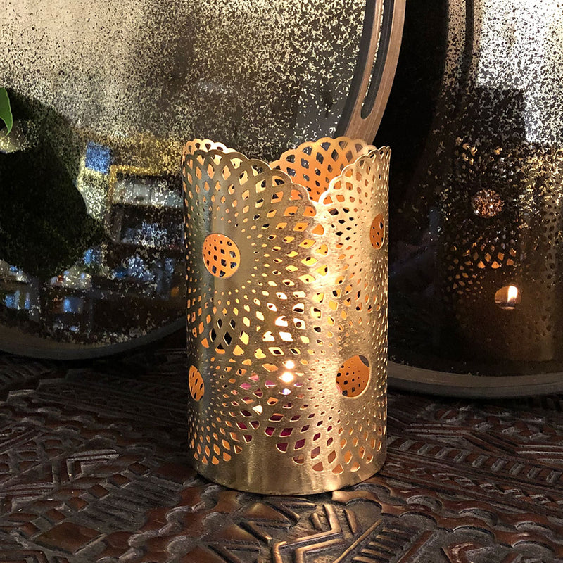golden metal tealight holder with open filigree work shown on console table with lit votive candle