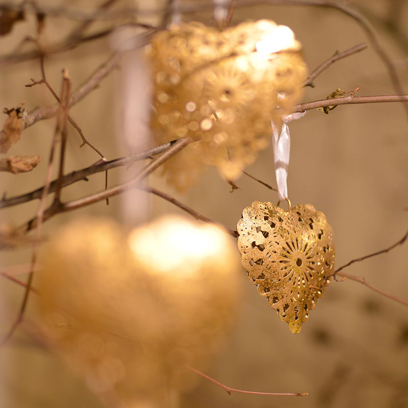 filigree gold hearts hanging on twigs catching the sunlight.