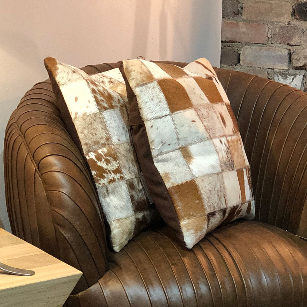 Cowhide cushion shown on brown leather chair.