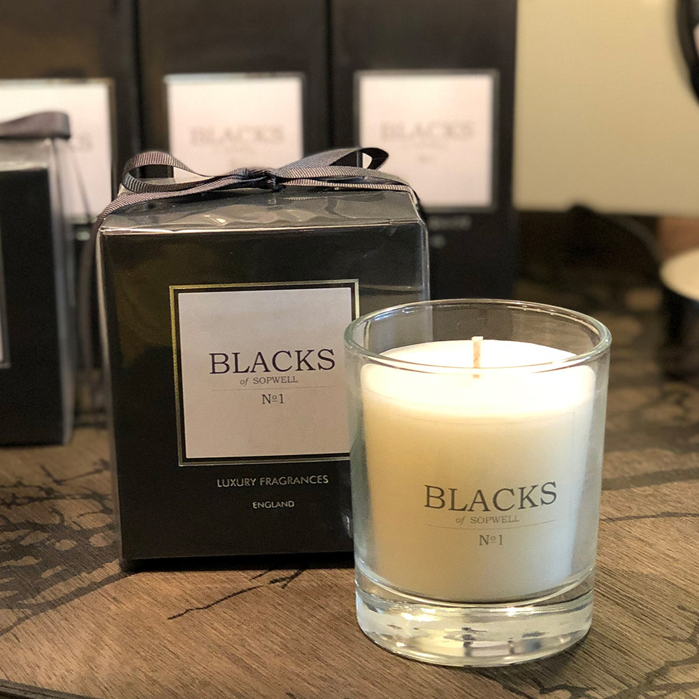 No1 scented candle, clear glass jar with white wax. next to black box packaging.