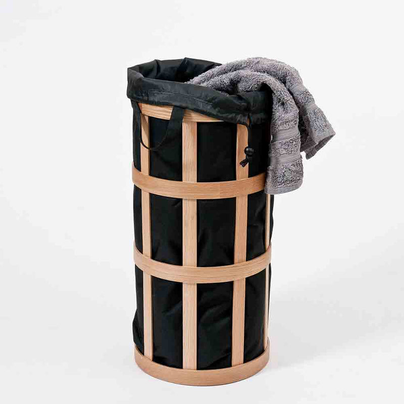 oak wood laundry bin with black inner bag, sown open with towel draping.