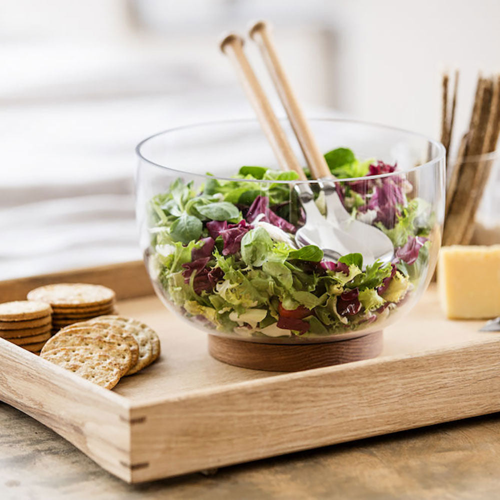 clear glass salad bowl, on solid oak round base. shown with salad leaves in.