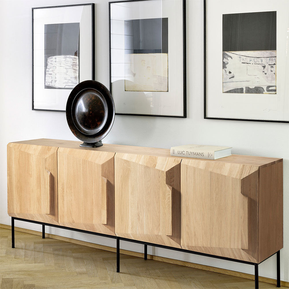 4 door sideboard with three pictures above. disc sculpture and book sit on top of sideboard
