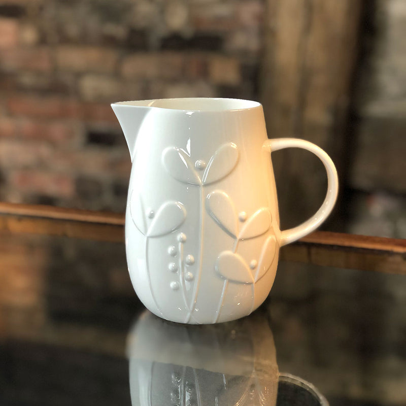 white bone china large jug with raised pattern of growing shoots and stems growing from the base