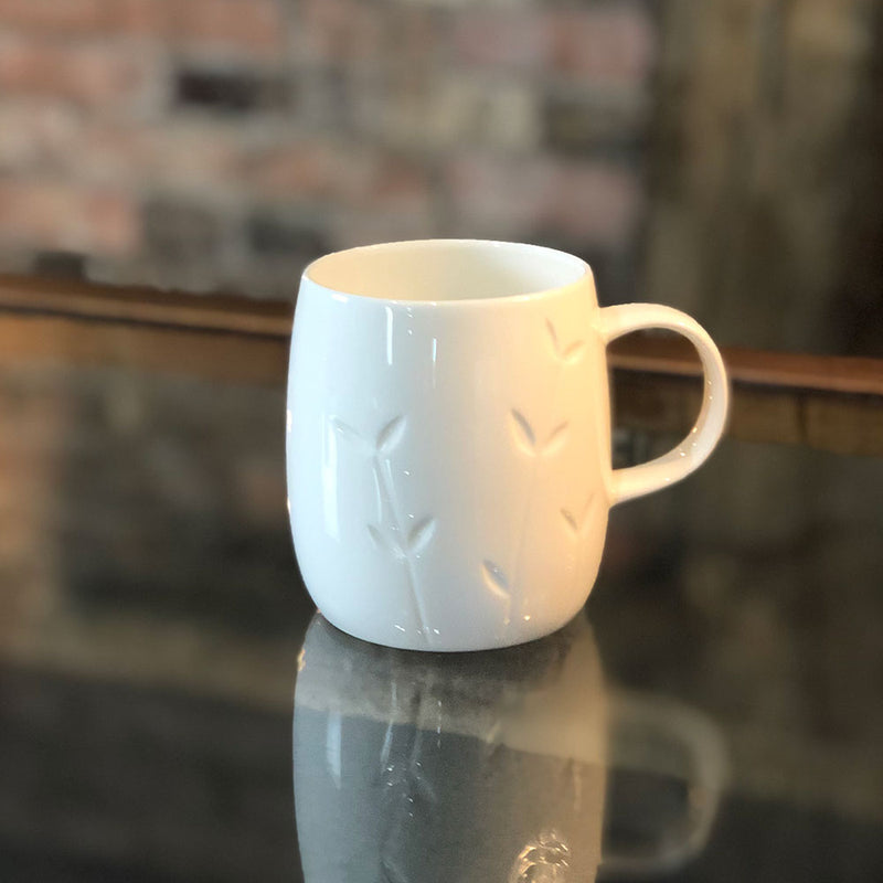 white bone china mug with indented design of growing leaves