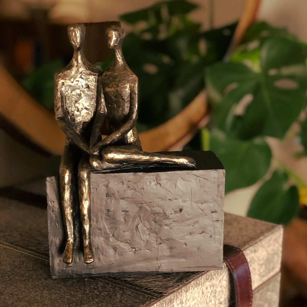 Seated couple sculpture, he is sitting on a large block, she is curled next to him, holding hands