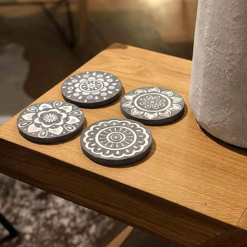 set of four round grey coasters with white circular pattern embossed