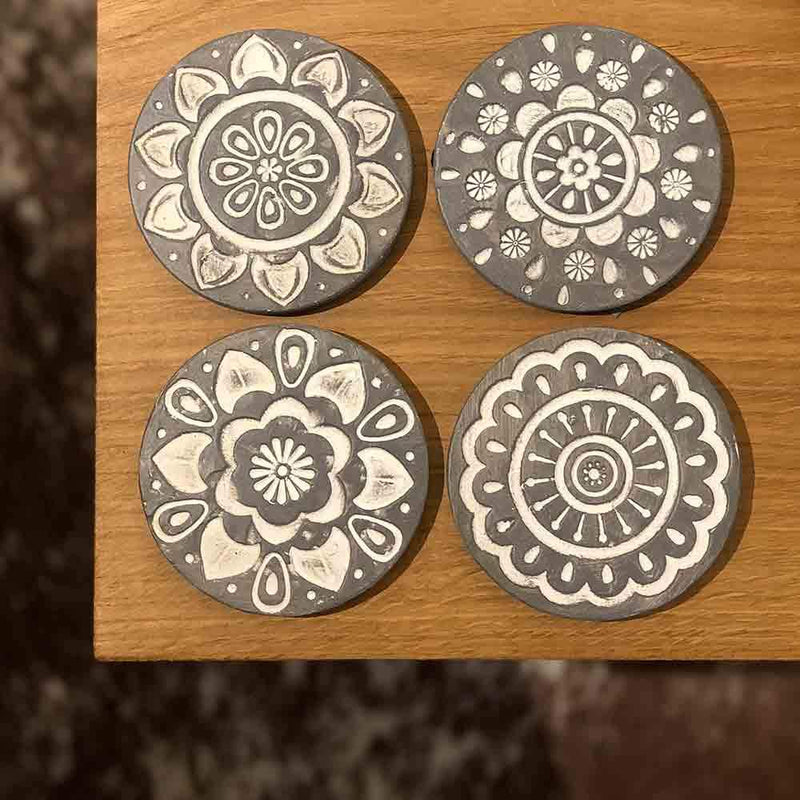 set of four round grey coasters with white circular pattern embossed, view from above