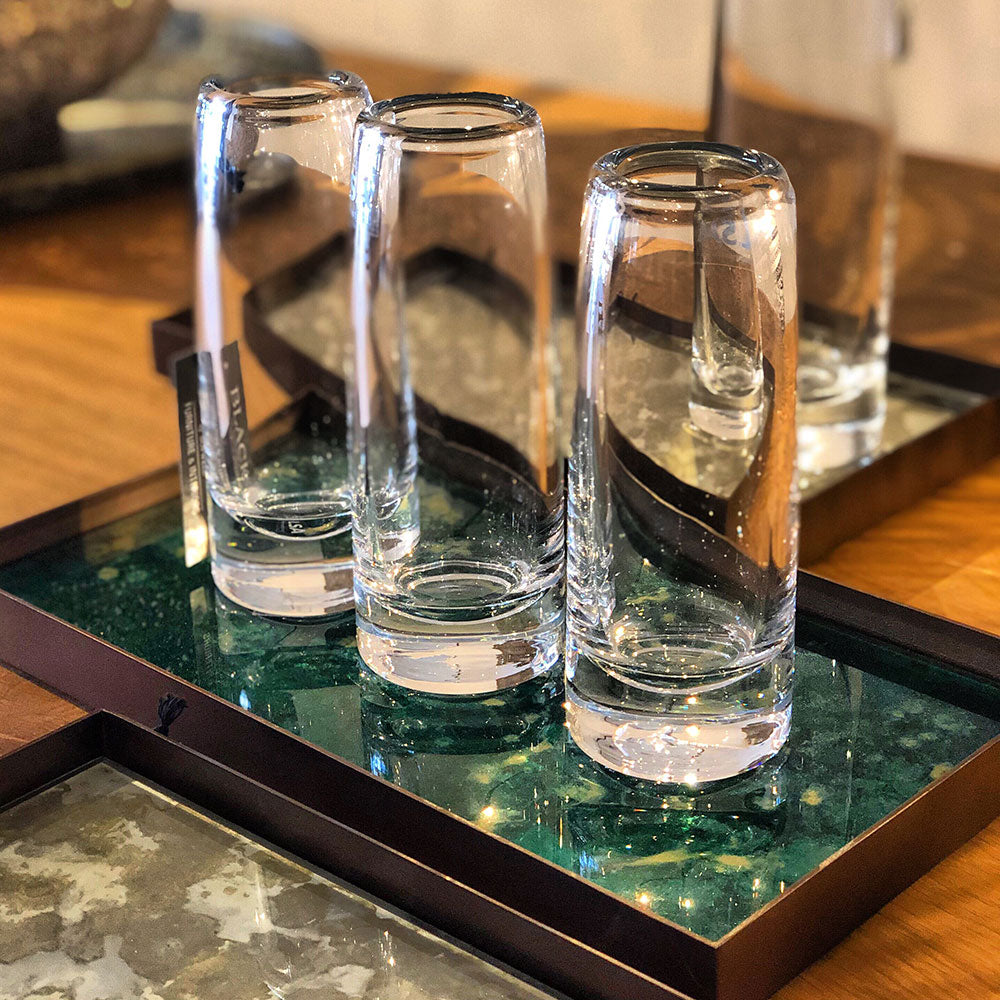 Glass bud vases lined up on a table tray.