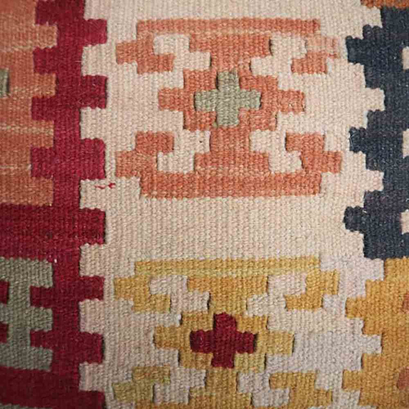 close up of woven kelim fabric seat- cream, red, navy, orange and pink pattern
