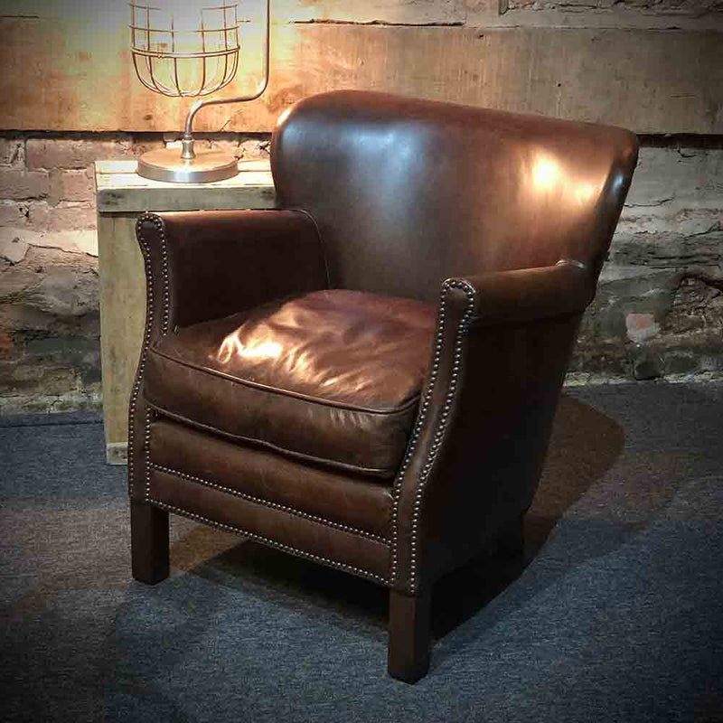 Studded arms and front on a classic chocolate brown leather armchair. leather side of the seat pad showing.