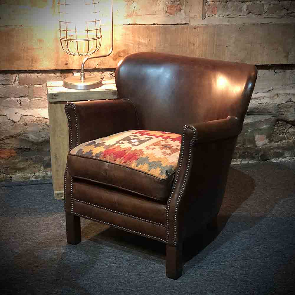 Studded arms and front on a classic chocolate brown leather armchair. Woven Kelim fabric seat.