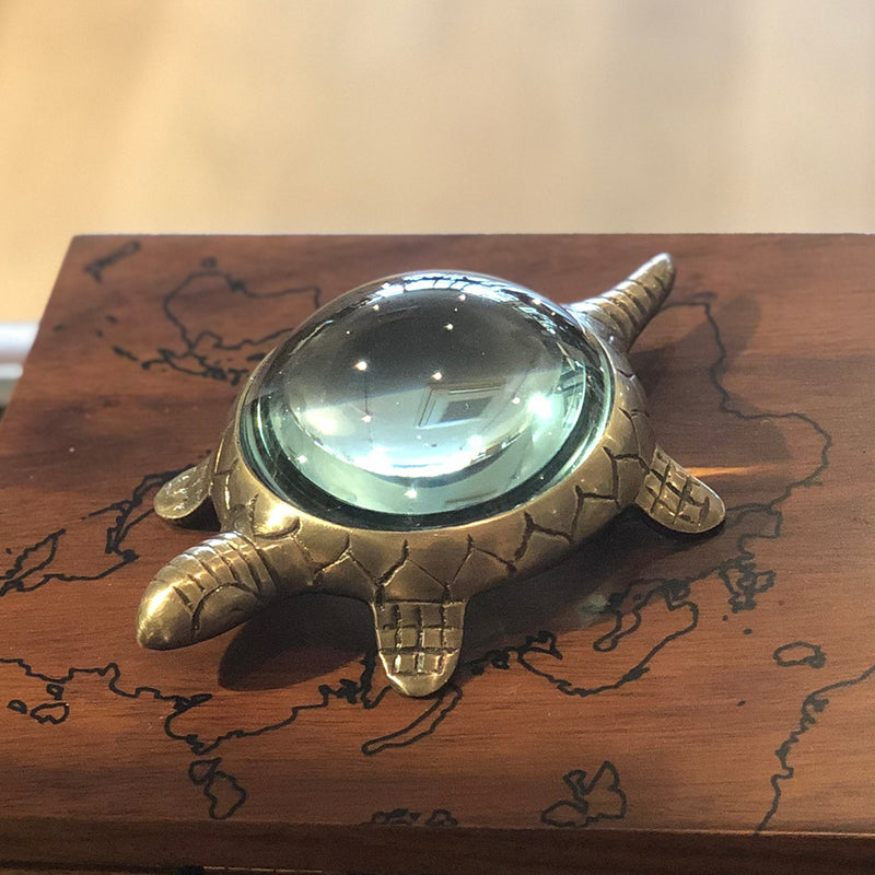 brass turtle stands on the desktop, his shell is a magnifying glass