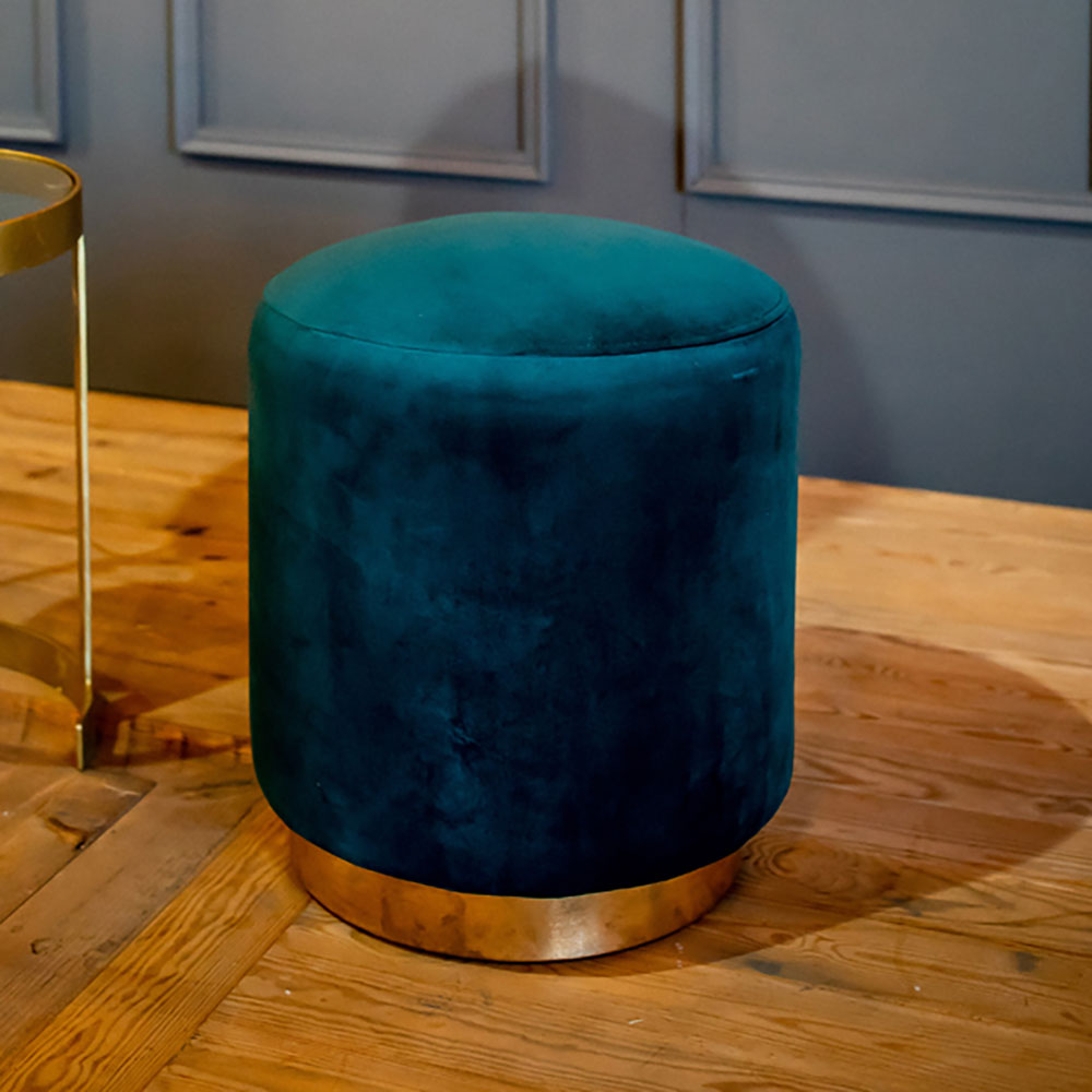 teal green velvet round stool, gold trim at base.