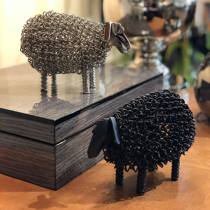 small wire ornaments, shaped like lambs. one shiny silver colour and one matt  black painted.