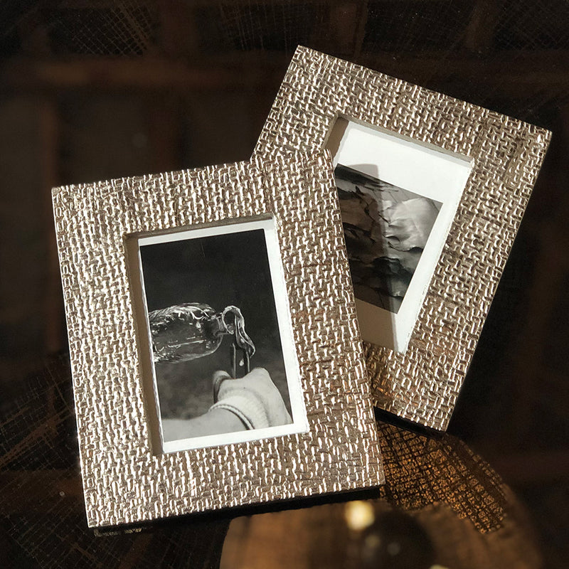 silver aluminium photo frame, with the effect of woven fabric. glass front , shown laying flat on a tray.