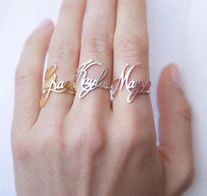 woman wearing custom cursive nametag rings in gold, rose gold and silver